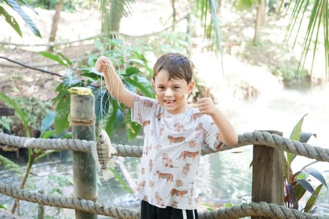 Henry fishing for tilapia at the chocolate farm